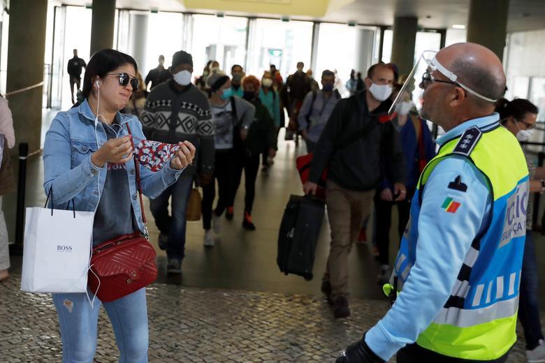 Полицейский просит женщину надеть защитную маску, поскольку Португалия облегчает блокировку на станции Cais do Sodre в Лиссабоне, 4 мая. REUTERS / Rafael Marchante