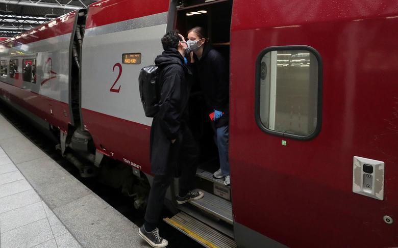 Француз Анри де Шасси в защитной маске целует своего партнера Марго Ребуа, который возвращается в Париж на скоростном поезде Thalys, проведя 2 месяца в Брюсселе, на станции Midi / Zuid в первый день смягчения меры по блокировке, в Брюсселе, Бельгия, 4 мая. REUTERS / Yves Herman & nbsp; & NBSP;