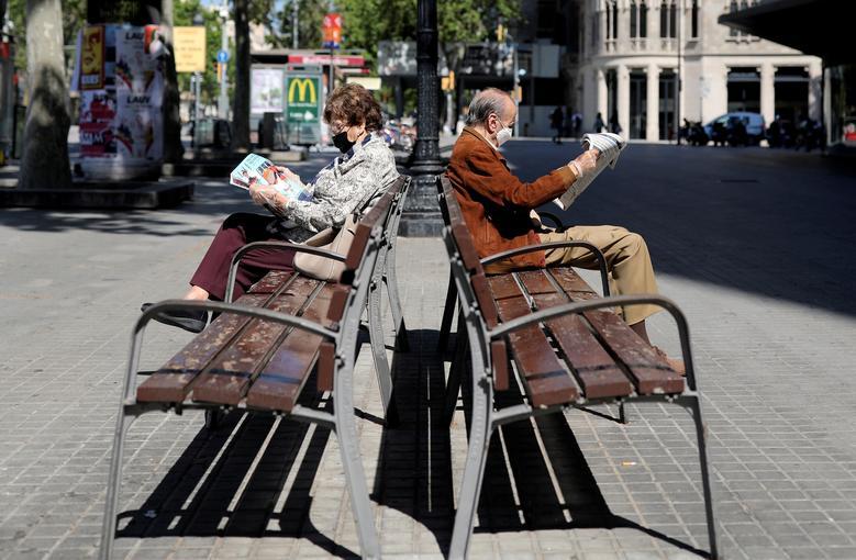 Пожилые люди в защитных масках читают газеты, сидя на скамейках в часы, в которые пожилым людям разрешается находиться на улице, в Барселоне, Испания, 4 мая. REUTERS / Nacho Doce & nbsp; & NBSP;