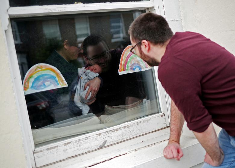 Уілл Уотсон дивиться у вікно на свою новонароджену племінницю, збираючи товари для будинку у своєї сестри в Стрітеме, південний Лондон, Великобританія, 18 квітня 2020 року. РЕЙТЕР / Ханна Маккей