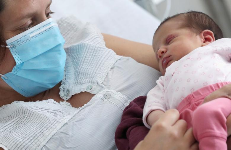 Амандин, чий тест на COVID-19 дав позитивний результат безпосередньо перед пологами, носить захисну маску для обличчя, тримаючи свою новонароджену дочку Махоут в лікарні CHIREC Delta в Брюсселі, Бельгія, 25 квітня 2020 року. Малюк махаута народився 23 квітня в Брюсселі від кесаревого розтину. через більш ранніх ускладнень, не пов'язаних з COVID-19, але які привели до тестування матері Амандин, хоча у неї не було ніяких симптомів. «Вони сказали мені, що перевірятимуть мене на наявність COVID-19, і я подумав, що це буде негативно. На наступний день мій гінеколог подзвонив мені, щоб сказати, що це позитивно, я мало не впав зі стільця », Амандин, яка попросила не дай їй прізвище, розповіла Reuters. Амандин, одягнена в блакитну медичну маску, що лежить на лікарняному ліжку і притискає дитину до грудей, сказала, що народжувати в самоті було важко. «Я так боявся за неї ...