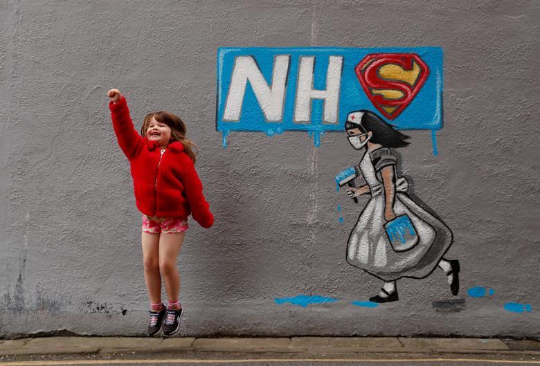 Лилли Давенпорт позирует своему отцу перед настенной росписью в честь Государственной службы здравоохранения США, написанной художником Рейчел Лист на стене паба Horse Vaults в Понтефракте, Великобритания, 4 апреля. REUTERS / Lee Smith & nbsp; & NBSP;