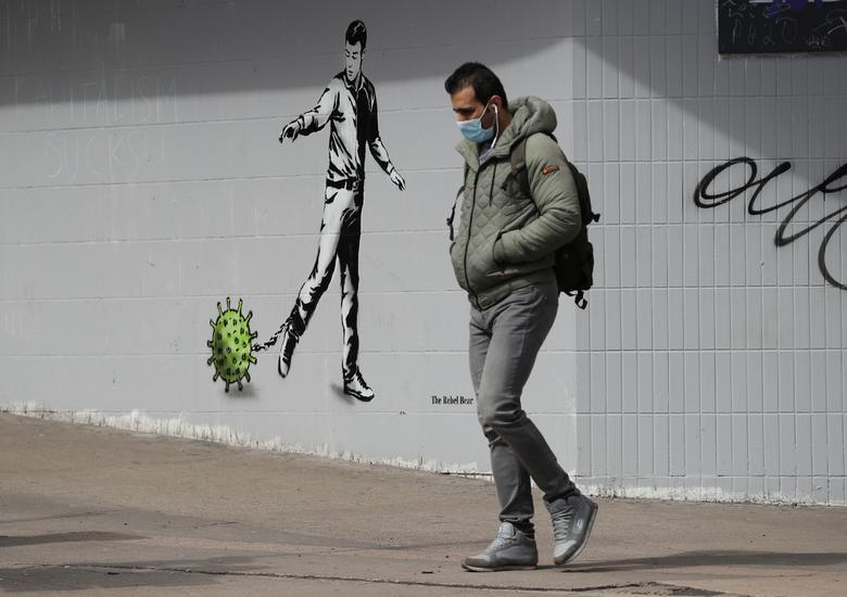 Мужчина в маске проходит мимо фрески в центре Глазго, 28 апреля. РЕЙТЕР / Рассел Чейн