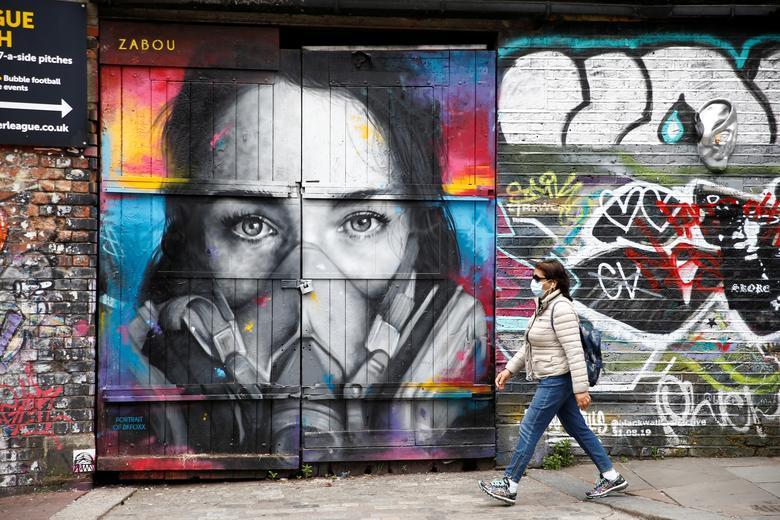 Женщина в защитной маске проходит мимо стрит-арта в Шордиче, Лондон, 10 мая. РЕЙТЕР / Генри Николс