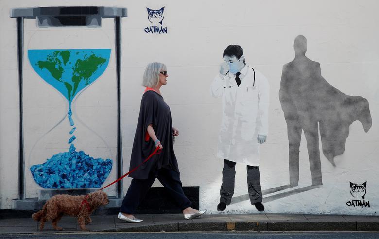 Женщина гуляет со своей собакой, когда она проходит мимо фрески Catman 'Superhuman' в Витстабле, Великобритания, 10 апреля. REUTERS / Peter Cziborra & nbsp;