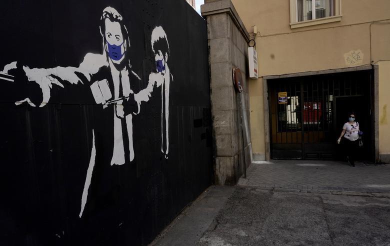 Женщина выходит из здания рядом с граффити, где изображены актеры из фильма «Криминальное чтиво» Джона Траволты и Сэмюэля Л. Джексона в защитных масках, Мадрид, Испания, 3 мая. РЕЙТЕР / Хуан Медина