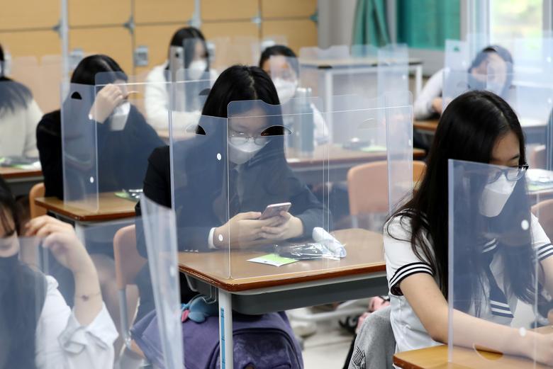 Ученики старших классов в лицевых масках готовятся к занятиям с пластиковыми чехлами на столах в Тэджоне, Южная Корея, 20 мая. Yonhap / via REUTERS