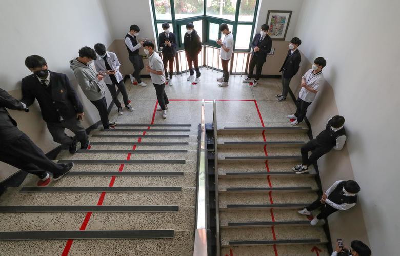 Ученики старших классов в защитных масках стоят в очереди, чтобы войти в кафетерий, так как школы открываются в Сеуле, Южная Корея, 20 мая. & Nbsp; Yonhap / via REUTERS & nbsp; & NBSP;