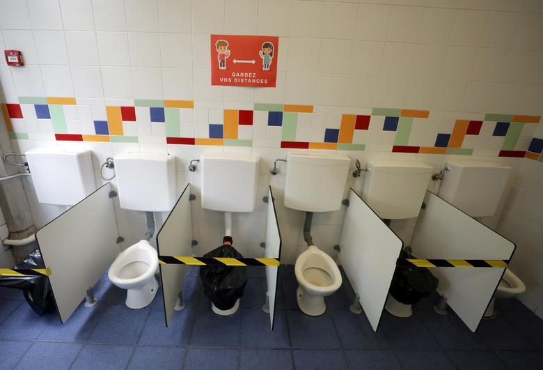 Надпись «Держите дистанцию» над туалетами в начальной школе накануне ее открытия в Ницце, Франция, 11 мая. REUTERS / Eric Gaillard