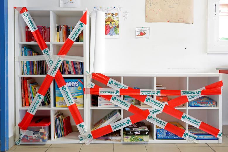 Полка с книгами и играми, которые не могут быть использованы детьми, защищена скотчем в классе в Сен-Себастьян-сюр-Луаре, недалеко от Нанта, Франция, 11 мая. REUTERS / Stephane Mahe