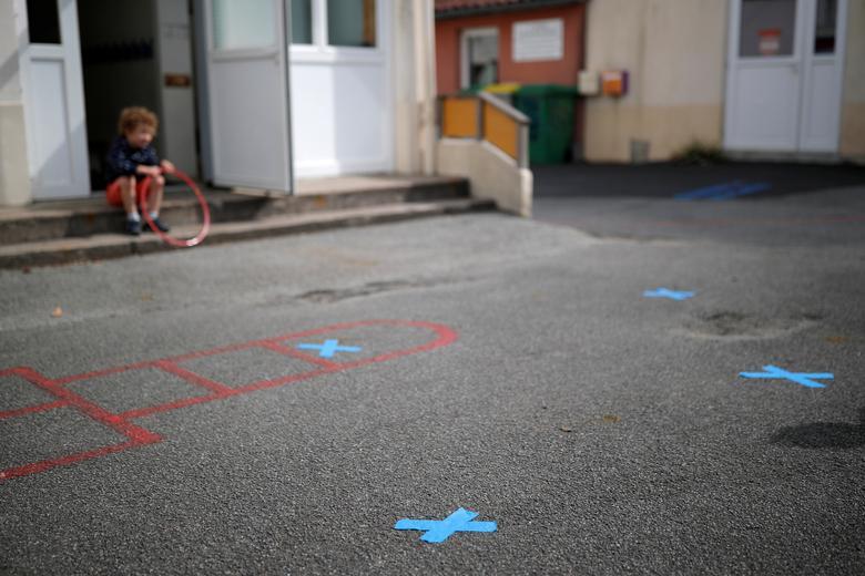 На подвір'ї приватної школи у дворі приватної школи під час її відкриття біля Нанта, Франція, 12 травня, видно ознаки підтримки соціальної ізоляції. РЕЙТЕР / Стефан Мае