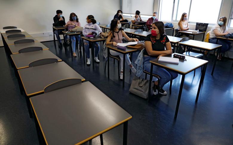 Ученики в защитных масках сидят в классе в средней школе им. Д. Педро V в Лиссабоне, Португалия, 18 мая. РЕЙТЕР / Рафаэль Марчанте