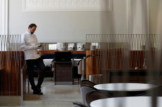 Chef and owner Daniel Humm looks at his phone in the shuttered dining room of Michelin starred restaurant Eleven Madison Park as the outbreak of the coronavirus disease (COVID19) continues in the Manhattan borough of New York, U.S., May 20, 2020.  Picture taken May 20, 2020. REUTERS/Lucas Jackson