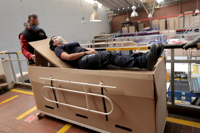 Rodolfo Gomez, a manager of the company ''ABC Display'' demonstrates how a hospital bed that the company manufactures is transformed into a cardboard coffin, amid the coronavirus disease (COVID-19) outbreak in Bogota, Colombia May 21, 2020.  REUTERS/Luisa Gonzalezz