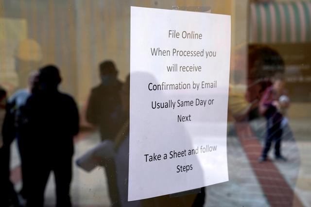 FILE PHOTO: People who lost their jobs are reflected in the door of an Arkansas Workforce Center as they wait in line to file for unemployment following an outbreak of the coronavirus disease (COVID-19), in Fort Smith, Arkansas, U.S. April 6, 2020. REUTERS/Nick Oxford -/File Photo/File Photo