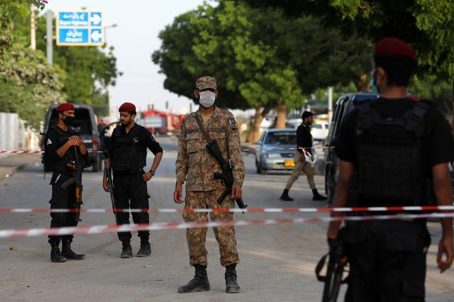 Army soldier and police officers guard a cordoned-off street leading to the site of a passenger plane crash in a residential area near an airport in Karachi, Pakistan May 23, 2020. REUTERS/Akhtar Soomro
