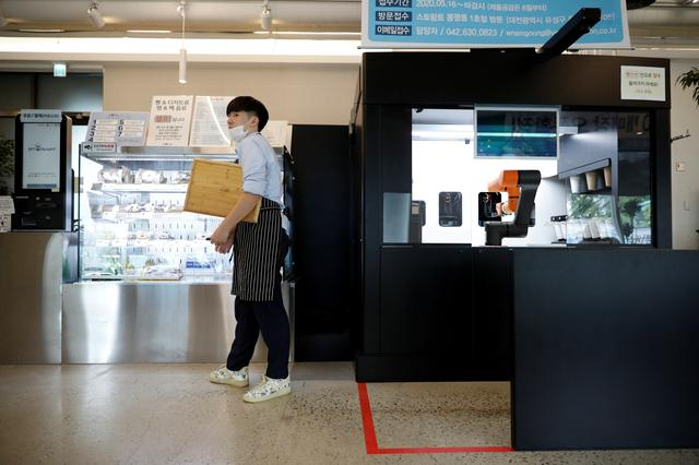 An employee stands next to a barista robot that takes orders, makes coffee and brings the drinks straight to customers in Daejeon, South Korea, May 25, 2020. REUTERS/Kim Hong-Ji