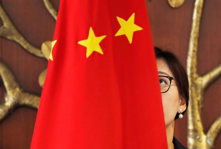 A Chinese official adjusts a Chinese flag before the start of a meeting...