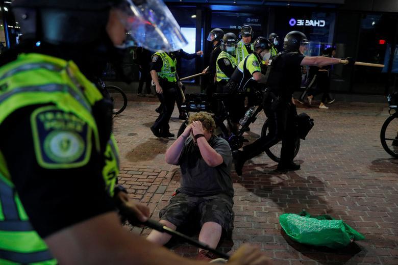 Polis, 31 Mayıs 2020'de Boston, Massachusetts'teki bir miting sonrasında coplarla indirdikleri bir protestocunun yanından geçiyor. & Nbsp;  REUTERS / Brian Snyder
