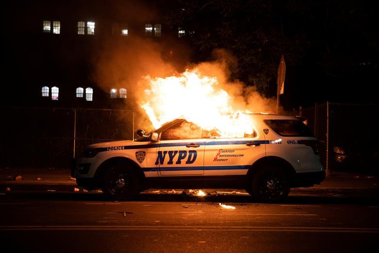 Protestocular 30 Mayıs 2020'de New York'un Brooklyn ilçesinde George Floyd'un Minneapolis polis nezaretinde ölüme karşı bir yürüyüş sırasında protestocuların polisle çatışması nedeniyle bir NYPD polis arabası ateşe verildi. REUTERS / Jeenah Moon