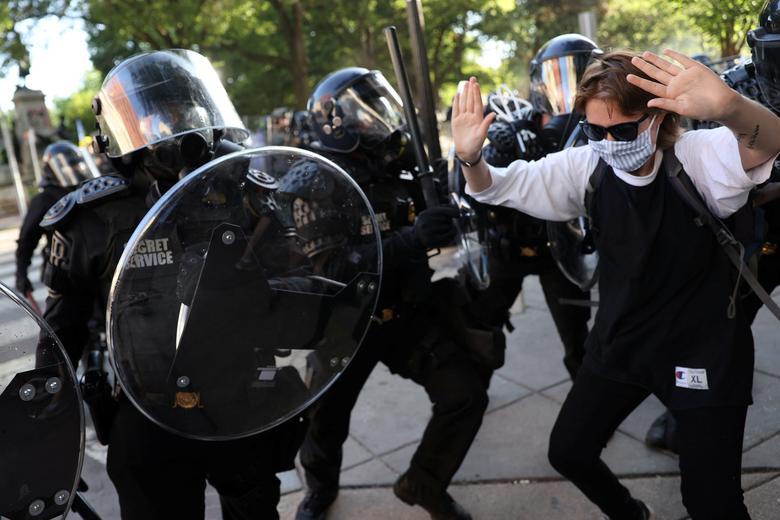 Beyaz Saray yakınlarındaki ABD Gizli Servisi üniformalı bölüm memurlarının yanında bir gösterici, 1 Haziran. REUTERS / Jonathan Ernst & nbsp;