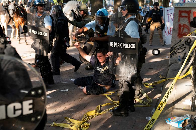 Çevik kuvvet polisi, Lafayette Parkı'nı ve çevresindeki alanı temizlemek için protestoculara koşarken bir adamı tutukladı, 1 Haziran. REUTERS / Ken Cedeno