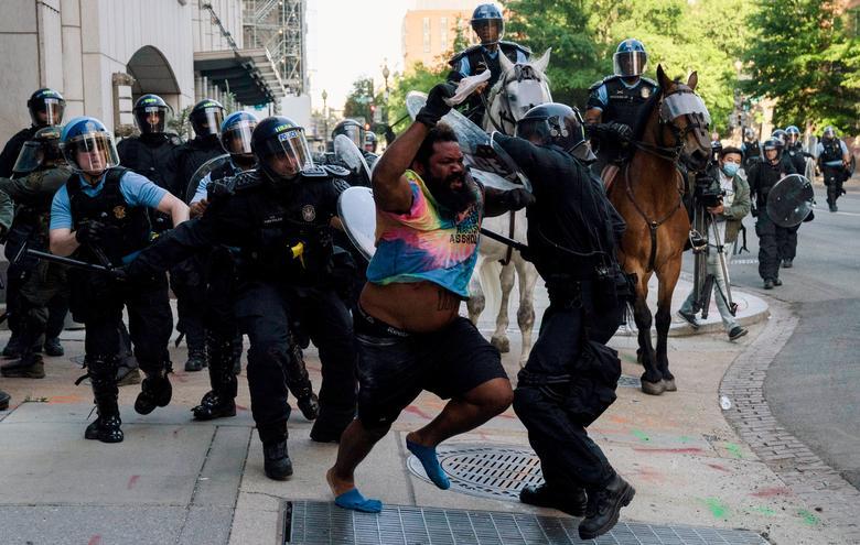 Çevik kuvvet polisi, Lafayette Park'ı ve çevresindeki alanı temizlemek için protestoculara koşarken bir adamı kovaladı. Başkan Trump'ın 1 Haziran'da fotoğraf fırsatı için yürüyebilmesi için REUTERS / Ken Cedeno & nbsp;