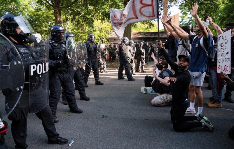 Protestocular, Lafayette Parkı ve çevresindeki bölgeden göstericileri temizlemek için çevik kuvvet polisinin önünde diz çöktüler, 1 Haziran. REUTERS / Ken Cedeno