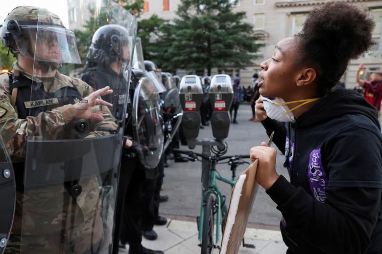 Bir gösterici Washington'daki Beyaz Saray yakınlarındaki bir miting sırasında kolluk kuvvetleriyle karşı karşıya. 1 Haziran. REUTERS / Jonathan Ernst & nbsp;  & Nbsp;