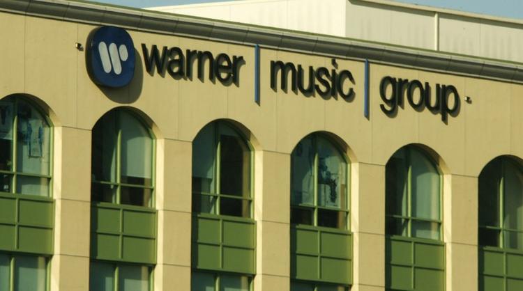 UPDATE 4-Warner Music strikes a chord as shares pop on Nasdaq debut