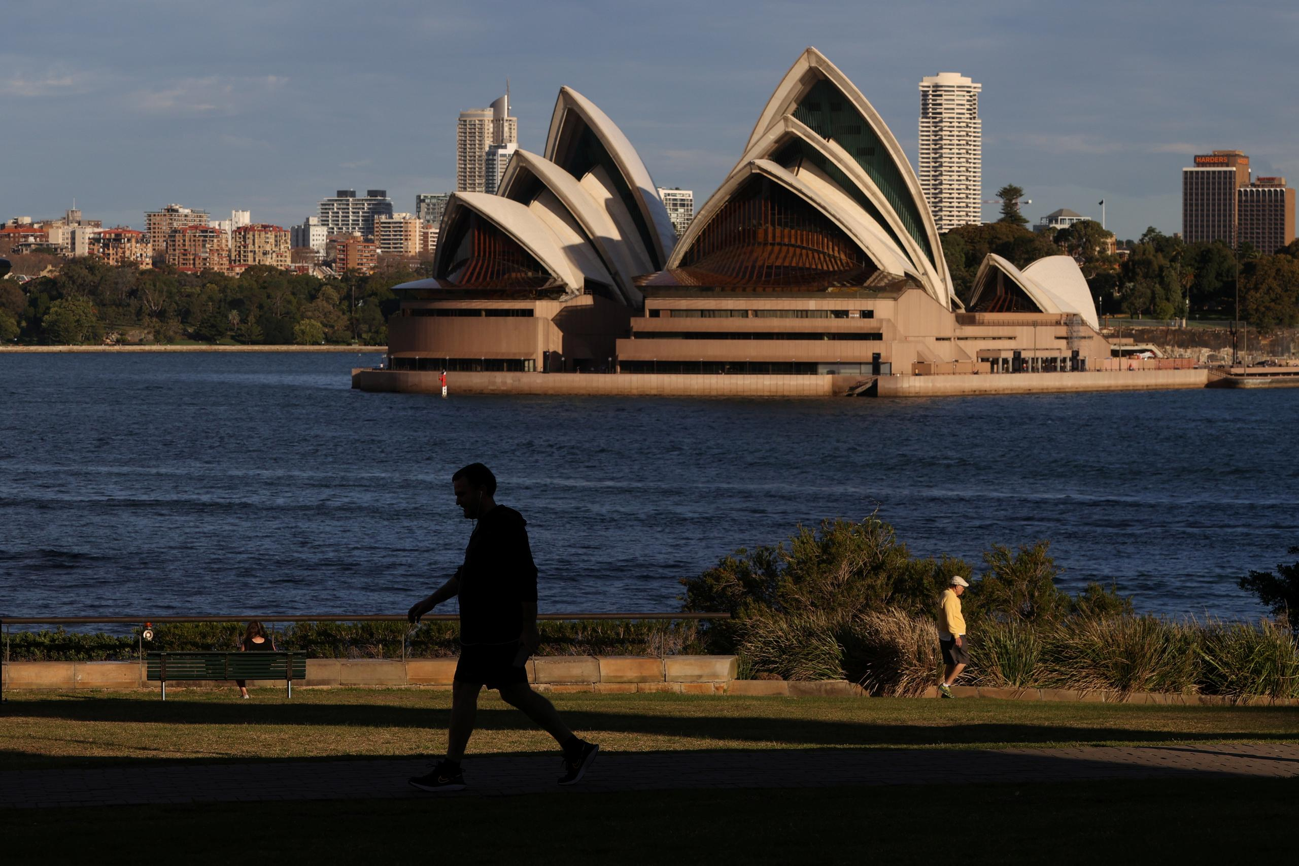 FILE PHOTO: People stroll through a park in front of the Sydney Opera House amidst the easing of the coronavirus disease (COVID-19) restrictions in Sydney, Australia, May 20, 2020. REUTERS/Loren Elliott