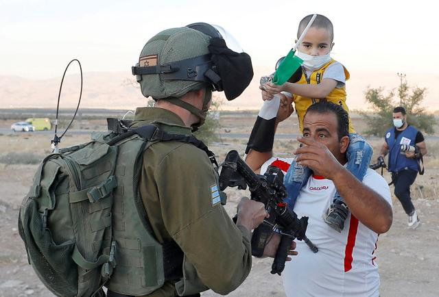A Palestinian man argues with an Israeli soldier during a protest against Israel\u0027s plan to annex parts of the occupied West Bank, in Jordan Valley June 24, 2020. REUTERS/Mohamad Torokman