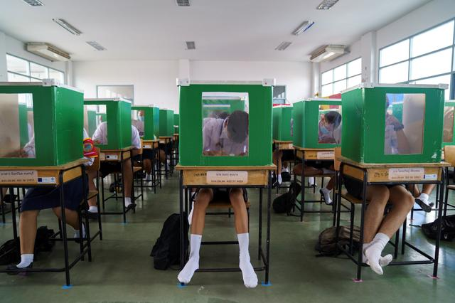Students of Sam Khok school, wearing face masks and face shields, are seen inside old ballot boxes repurposed into partitions as they attend a class after the Thai government eased isolation measures and introduced social distancing as schools nationwide reopen, at Pathum Thani province, Thailand, July 1, 2020. REUTERS/Athit Perawongmetha