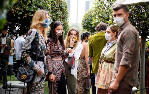 Masked fashionistas and distant models at first COVID-era fashion shows in Milan