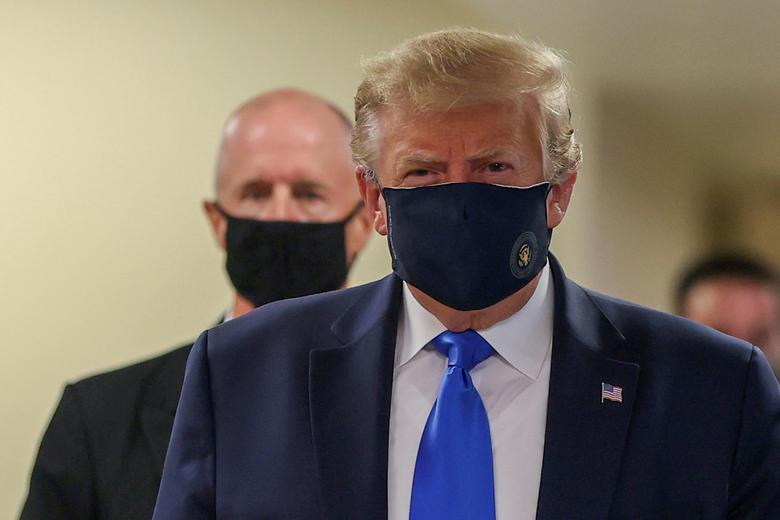 U.S. President Donald Trump wears a mask while visiting Walter Reed National Military Medical Center in Bethesda, Maryland, July <span dir=