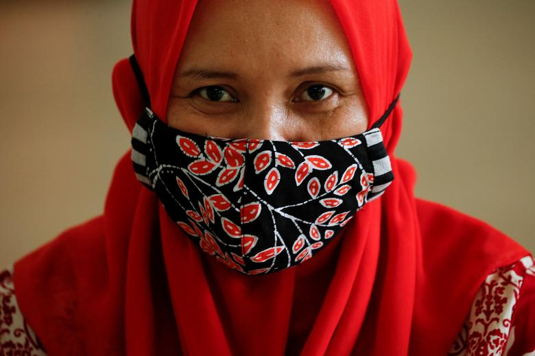 A woman wearing a protective mask painted with Indonesian traditional batik looks on at a workshop in Jakarta, Indonesia, July 1, <span dir=