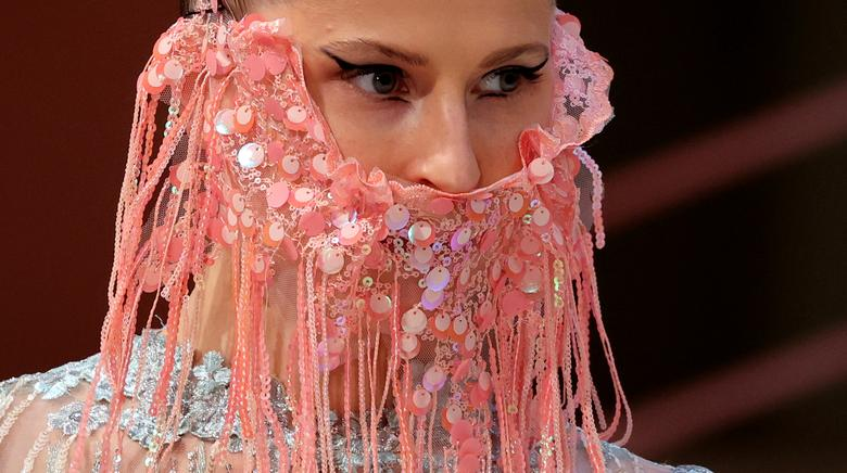 A model wears a face mask as she presents creations of the <span dir=