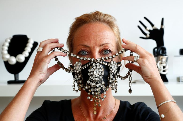 Belgian jewellery designer Olivia Hainaut poses wearing a protective mask decorated with gems in her workshop in Brussels, Belgium July 22, <span dir=