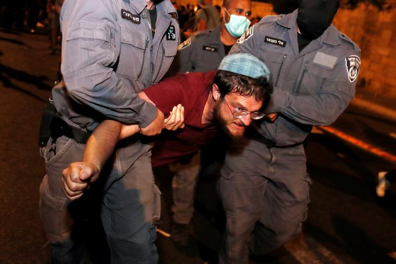 Israeli Police detain a man during a protest against Israeli Prime Minister Benjamin Netanyahu's alleged corruption and his government's handling of the coronavirus crisis, near his residence in Jerusalem July 26, <span dir=