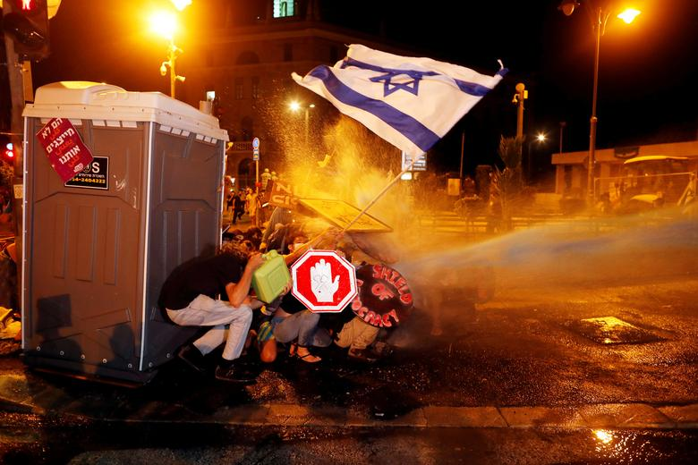 Police use a water cannon during a protest against Israeli Prime Minister Benjamin Netanyahu's alleged corruption and his government's handling of the coronavirus crisis, near his residence in Jerusalem July 26, <span dir=