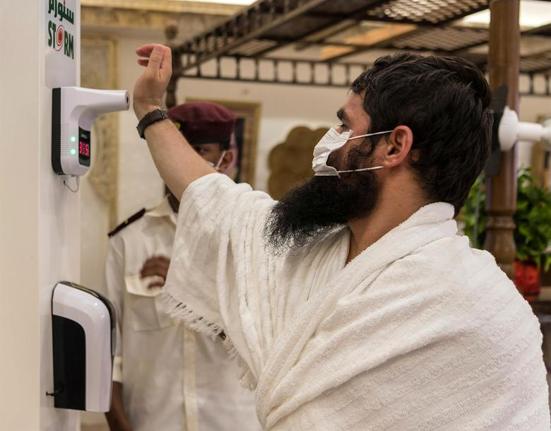 A Muslim pilgrim wearing a protective face mask has his temperature checked as he arrives in Mina, July 29, <span dir=