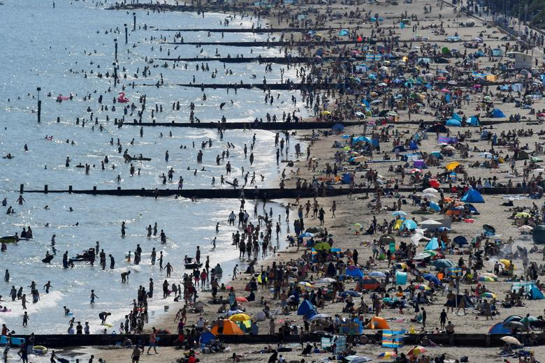 People are seen on the beach in Bournemouth as they enjoy the hot weather in Britain, June 2. REUTERS/Toby Melville