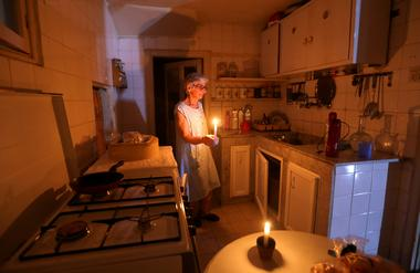 FILE PHOTO: Samira Hanna,70, walks in her kitchen as she holds a candle due...