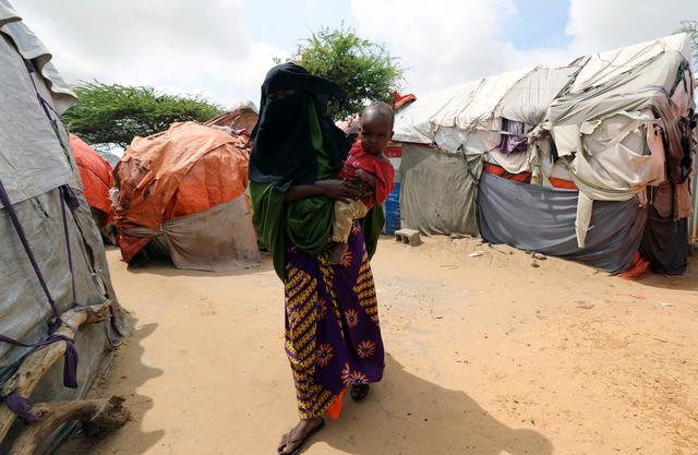 Zahra Ahmed Bawe, 14, a Somali girl carries her 2-year-old son as she walks within makeshift shelters at the Alafuuto camp for internally displaced persons in Garasbaaley district of Mogadishu, Somalia August 14, 2020. Picture taken August 14, 2020. REUTERS/Feisal Omar