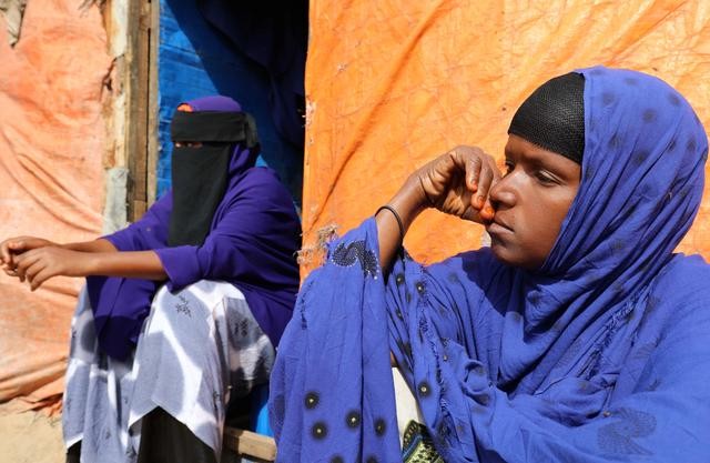 Faadumo Ali Fiidow (R) sits with her daughter Hafsa Ali Osman, 15, who is suspected of being forced into marriage, sits outside her makeshift shelter at the Alafuuto camp for internally displaced persons in Garasbaaley district of Mogadishu, Somalia August 14, 2020. Picture taken August 14, 2020. REUTERS/Feisal Omar