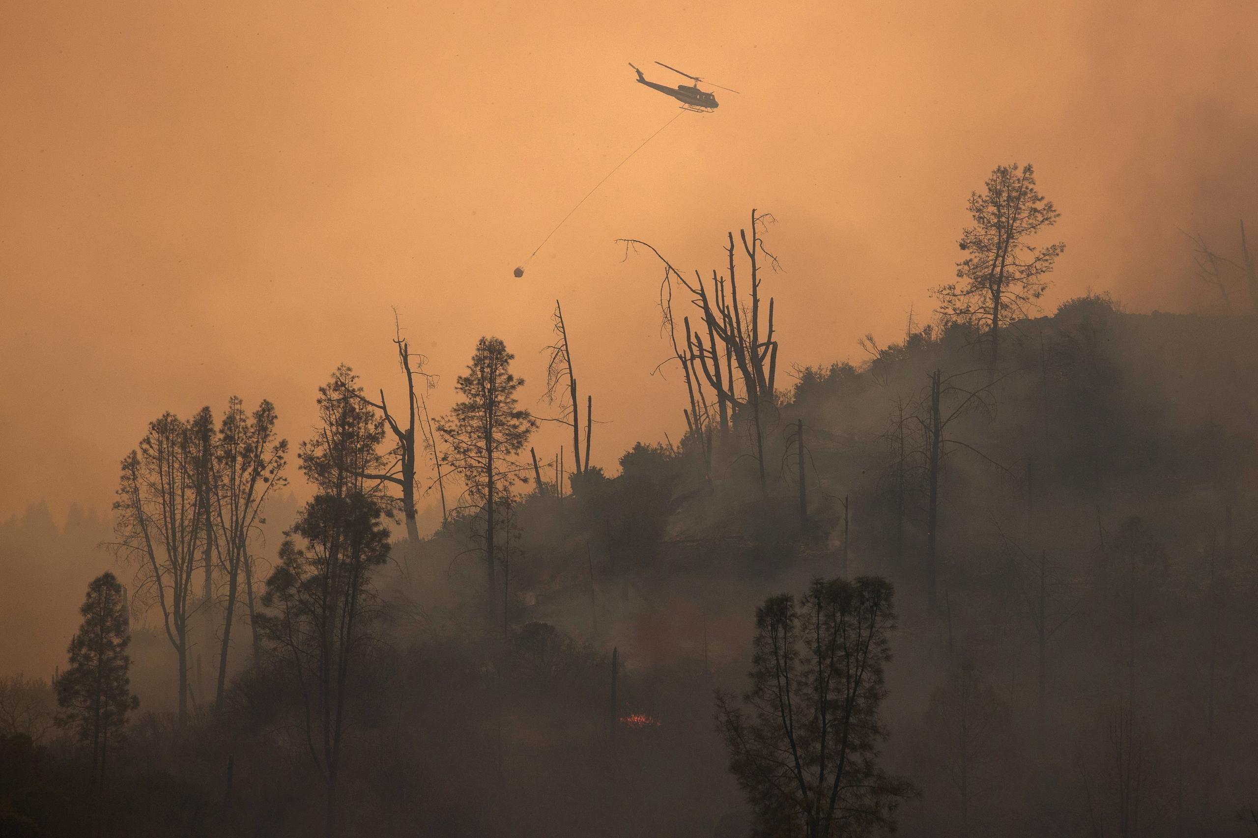 FILE PHOTO: A helicopter and crew releases water to extinguish a section of the LNU Lightning Complex Fire near Middletown, California, U.S. August 24, 2020. REUTERS/Adrees Latif