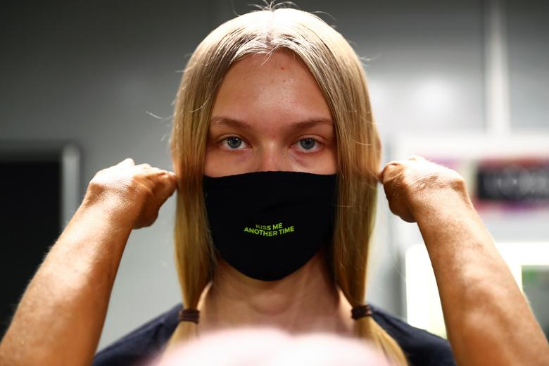A model wears a protective face mask in the backstage before the Andres Sarda show. REUTERS/Sergio Perez