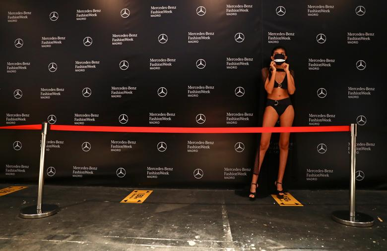 Social distancing signs are pictured as a model wears a protective face mask before the Andres Sarda show.  REUTERS/Sergio Perez