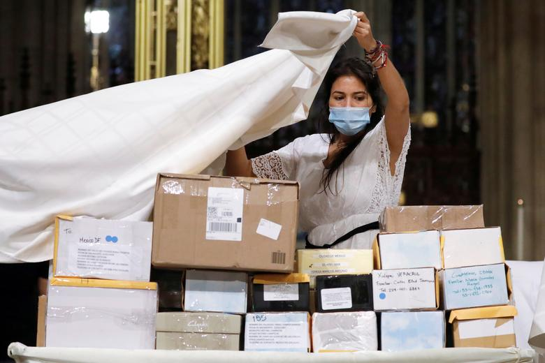 A woman covers boxes containing human remains before a prayer service at Saint Patrick's Cathedral, held to bless the ashes of Mexicans who died during the coronavirus outbreak but could not have a funeral Mass or burial, in Manhattan, New York, July 11. REUTERS/Andrew Kelly