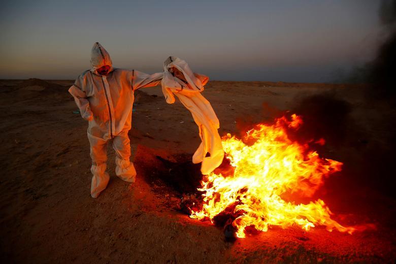 A member of the Popular Mobilization Forces (PMF), who volunteered to work in a cemetery, burns clothes they used for burial, near the new Wadi Al-Salam cemetery dedicated to those who died of the coronavirus, on the outskirts of the holy city of Najaf, Iraq May 25. REUTERS/Alaa al-Marjani